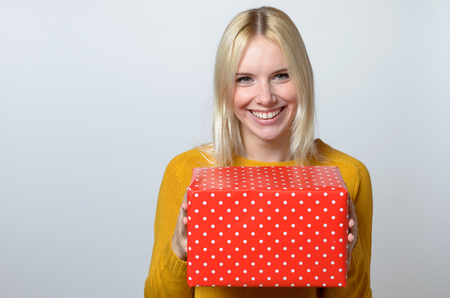 speculate: Happy Blond Young Woman Holding Red Gift Box Against White Background.