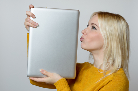 techie: Happy Young Woman Kissing the Edge of her Laptop Computer with open Eyes Against White Background.