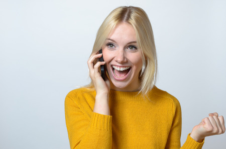 half body: Half Body Shot of a Happy Young Woman Talking to Someone Over the Mobile Phone, Showing a Toothy Smile. Stock Photo