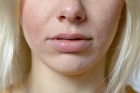 unemotional: Close up Bare Lips and Nose of a Young Blond Woman