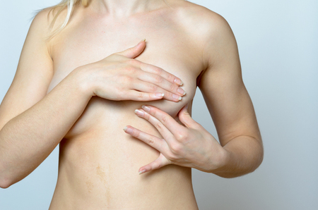 seni: Close up Bare Woman Holding her Chest for Breast Cancer Concept Against Gray Background.