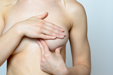 Young woman doing a breast examination massaging and manipulating her bosom to detect any early signs of a cancer tumour close up of her bare breast and hands