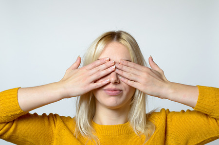 hands covering eyes: Close up Young Woman Covering her Eyes with Bare Hands Against Gray Background.