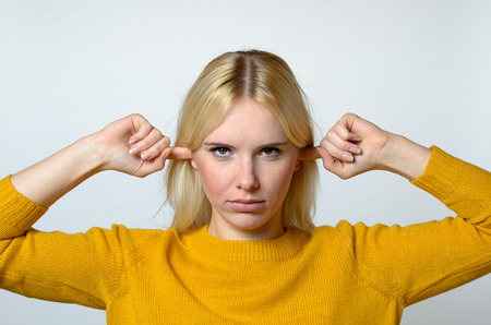 eyes opened: Close up Disgusted Young Woman Covering her Ears with Fingers, with open Eyes, Against Gray Background.