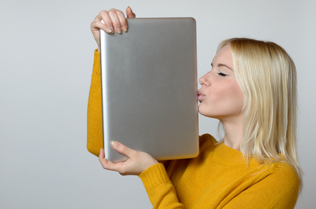 techie: Happy Young Woman Kissing the Edge of her Laptop Computer with Eyes Closed Against White Background.