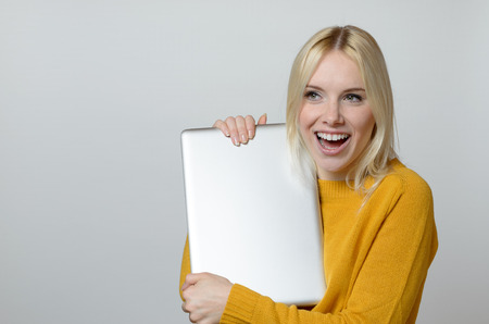 mouth  open: Very Happy Young Woman Holding a Brand New Laptop Computer with Mouth Open Against White Background