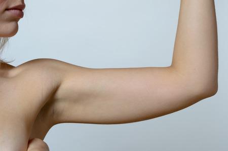 elasticidad: Mujer rubia joven que muestra el brazo flácido, efecto del envejecimiento causado por la pérdida de elasticidad y el músculo, primer plano