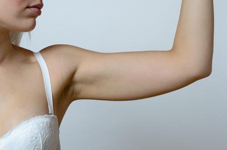 elasticidad: Mujer rubia joven que llevaba sujetador de encaje blanco, mientras que muestra el brazo flácido, efecto del envejecimiento causado por la pérdida de elasticidad y el músculo, primer plano