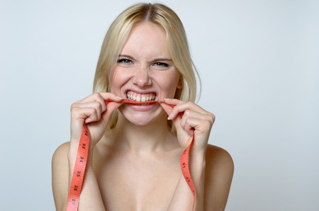 body expression: Close up Shirtless Young Woman Biting a Measuring Tape and Looking at the Camera Against Gray Wall Background.