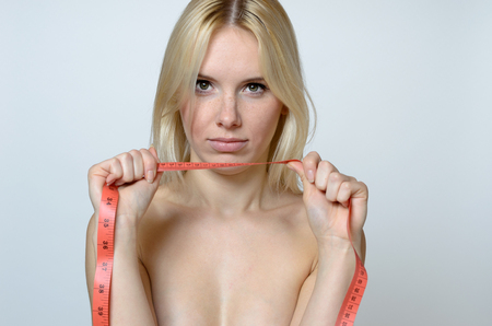 expresion corporal: Close up Shirtless Young Woman holding a Measuring Tape and Looking at the Camera Against Gray Wall Background.