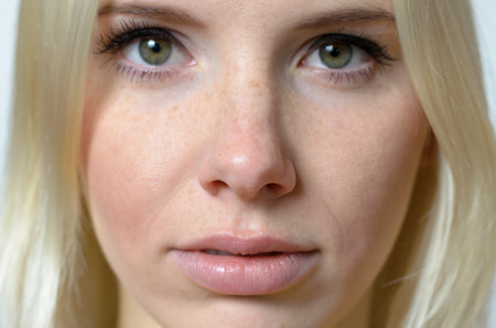 unemotional: Close up Serious Face of a Blond Young Woman with No Make-up, Staring at the Camera