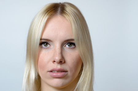 deadpan: Close Up Serious Pretty Face of a Blond Young Woman Staring at the Camera Against Gray Wall Background