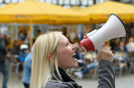 verbal: Woman yelling into a megaphone on an urban street voicing her displaeasure during a protest or demonstration, close up side view of her face
