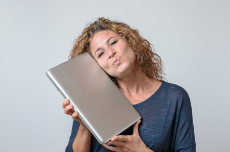 kissing mouth: Very Happy Young Woman Holding a Brand New Laptop Computer with Mouth like kissing Against White Background Stock Photo