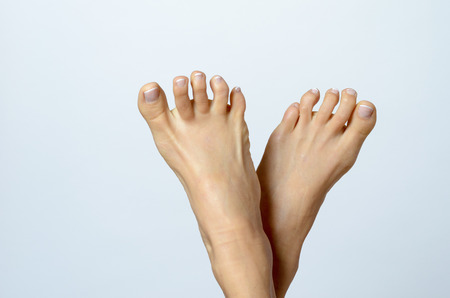 feet naked: Close up Bare Feet of a Woman Pointing Up Against Gray Background with Copy Space.