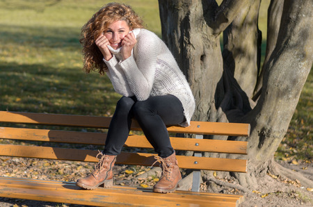 sweater girl: Young woman sitting on a bench in front of a tree while looking in to the camera Stock Photo