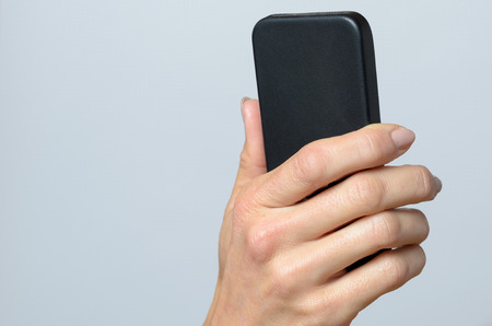 cell phone screen: Hand holding a black cellular Against Gray Background with Copy Space.