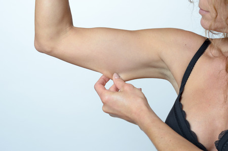 ageing: Middle aged woman displaying the loose skin or flab due to ageing on her upper arm pinching it between her fingers, close up view Stock Photo