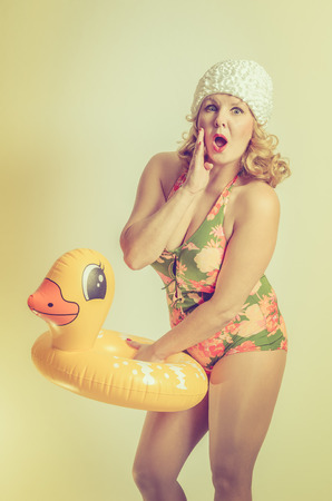 yellow duck: Shocked Young Woman holding a duck lifebelt in her hands, pin-up style