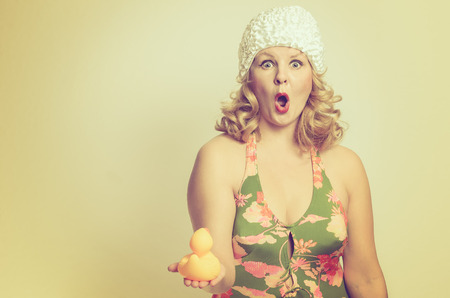 open girl: Shocked young woman holding a duck in her hand with her mouth wide open, pin-up style