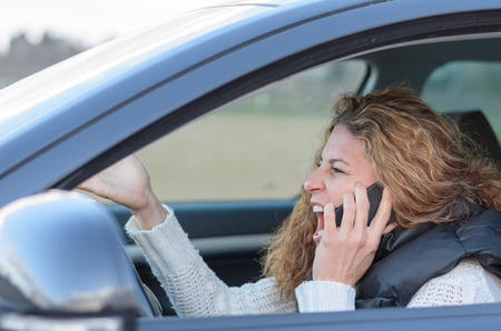 woman ist driving her car very aggressive and having a call