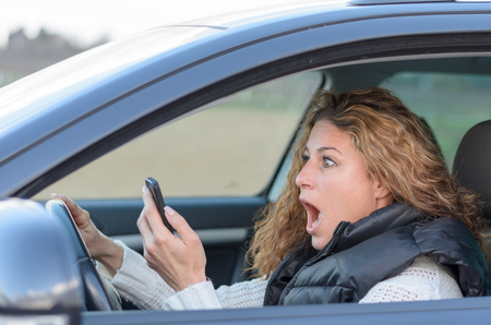 woman ist driving her car and looking shocked on her mobile