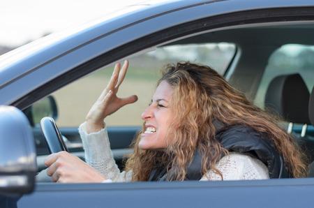 彼の拳で女性彼女の非常に積極的な車と与える運転 ist ジェスチャーします。
