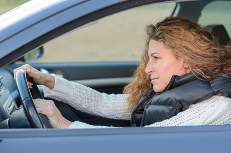 honking: woman ist driving her car and pushing the horn Stock Photo