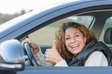 ist: woman ist driving her car and giving a thumb up gesture