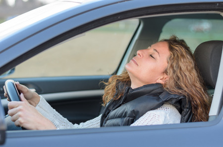 woman ist driving her car and is falling to sleep Фото со стока