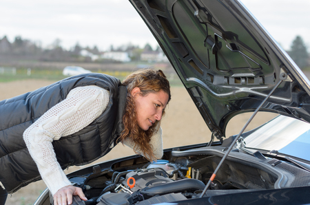 car trouble: woman s car breaks down and she is looking at the motor