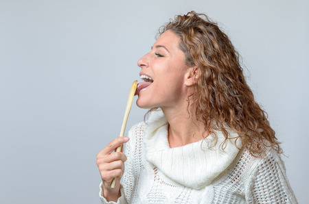 happy middle aged woman licking with her tongue at a wooden spon