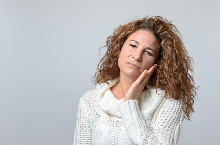portrait of woman: Worried middle aged woman looking at the camera with her hand raised to her cheek and a pained serious expression, over grey with copyspace Stock Photo