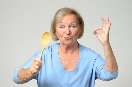 cook: Senior cook or housewife showing her approval of a recipe as she holds a wooden spoon in one hand while making a perfect gesture with the other, over grey Stock Photo