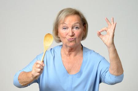 Senior kok of huisvrouw toont haar goedkeuring van een recept als zij in het bezit van een houten lepel in de ene hand, terwijl het maken van een perfecte gebaar met de andere, over grijs Stockfoto
