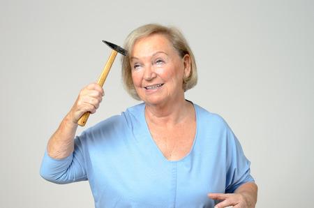 高齢者女性のグレーで、上半身の概念的なイメージで苦悩の表情で小さなハンマーで頭を打つ