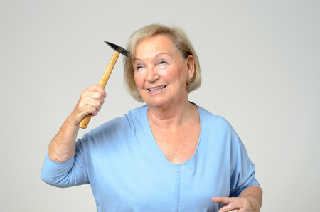 Elderly lady hitting her head with a small hammer with a look of anguish in a conceptual image, upper body over grey Banco de Imagens