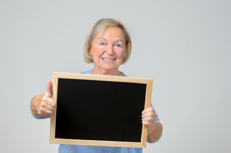 beaming: Enthusiastic elderly woman with a blank blackboard or slate that she is holding in front of her chest with a beaming smile , copyspace for your text Stock Photo