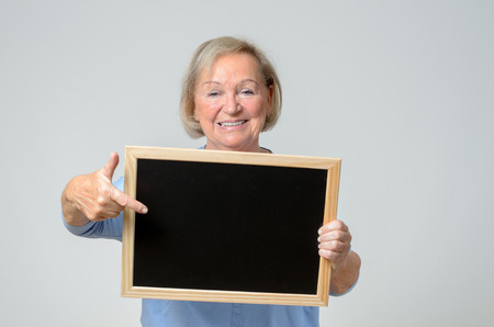 beaming: Enthusiastic elderly woman pointing to a blank blackboard or slate that she is holding in front of her chest with a beaming smile , copyspace for your text