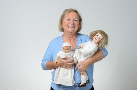 adult toys: Elderly woman holding two antique dolls in her arms with a smile, conceptual of a collector or of a woman reminiscing her childhood, over grey