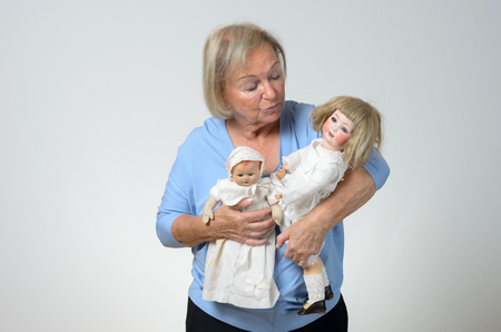 cradling: Elderly woman holding two antique dolls in her arms, conceptual of a collector or of a woman reminiscing her childhood, over grey