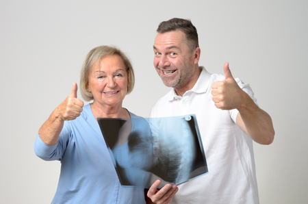 thumb x ray: Doctor discussing an x-ray with an elderly female patient as they stand side by side over a grey background in a healthcare and medical concept, while giving thumb up gesture