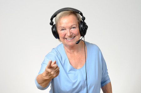 entertainment background: Excited senior woman listening to music on a set of stereo headphones smiling with enjoyment and pointing at the camera, over grey