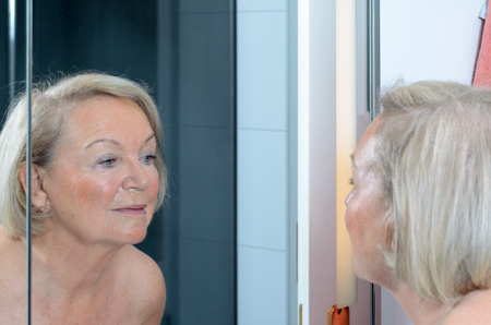 Senior lady checking her skin in the mirror leaning forwards for a closer look