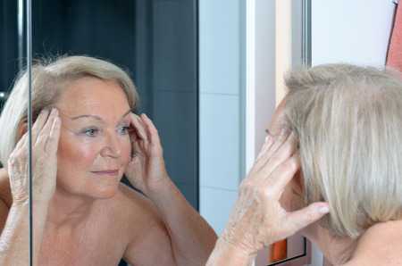 oldage: Senior lady checking her skin in the mirror leaning forwards for a closer look as she hold both hands to her forehead