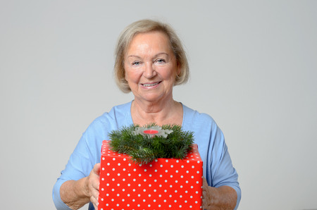 giftwrapped: Attractive elderly lady with a large gift-wrapped red Christmas gift offering it to the camera with a warm friendly smile, over grey Stock Photo