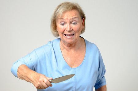 brandishing: Emotional elderly woman brandishing a kitchen knife in her hand with a look of perplexed horror and shock, over grey