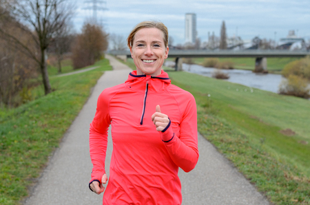 femme blonde: Sportif Moyen femme blonde �g�e de jogging le long de la digue et souriant � la cam�ra.