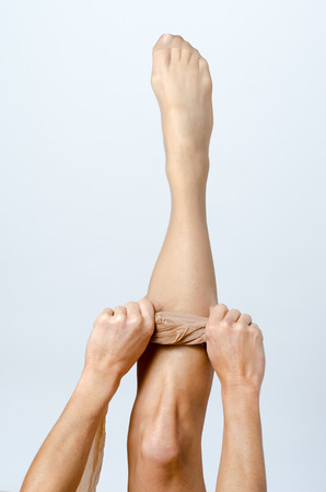 female sex: young Woman pulls her nylon stockings on, conceptual of a female sex symbol, closeup body view over grey