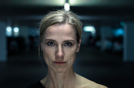 introspective: Night portrait of an attractive intense middle-aged blond woman looking directly into the camera, head and shoulders in shadows outdoors